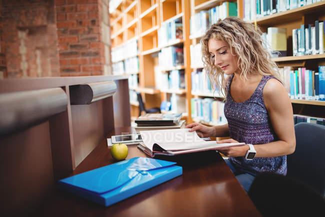 Mulher sentado e lendo livro na biblioteca — Fotografia de Stock