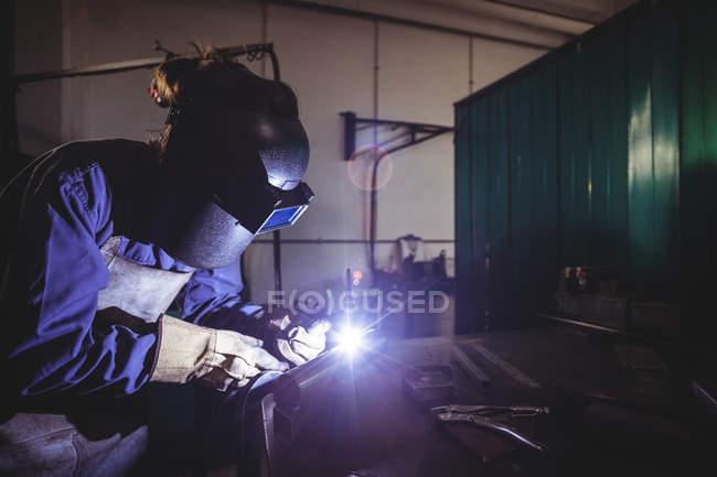 Женщина-сварщик работает на куске металла в мастерской — стоковое фото
