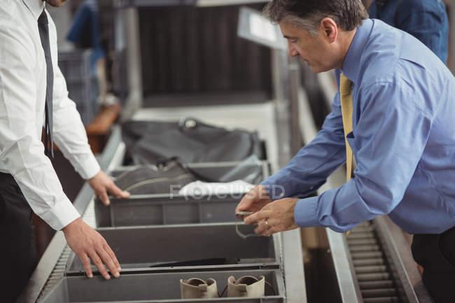 Homem colocar o relógio na bandeja para verificação de segurança no aeroporto — Fotografia de Stock