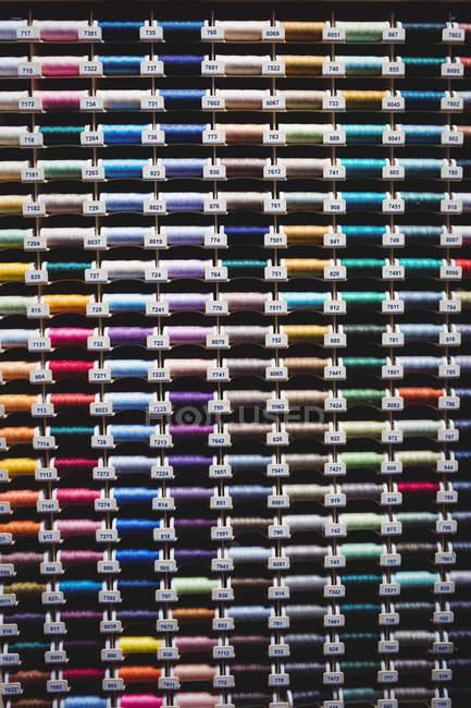 Bobines colorées de fils en boîte en studio de couture — Photo de stock