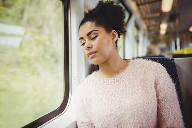 Красива жінка, що спить сидячи в поїзді — стокове фото