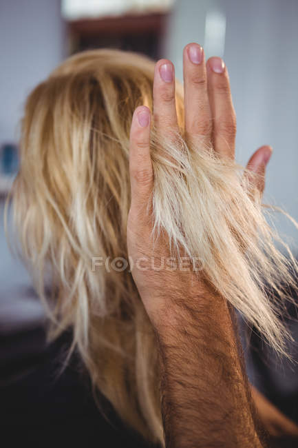 Cropped image of Hair stylist styling woman hair in salon — Stock Photo