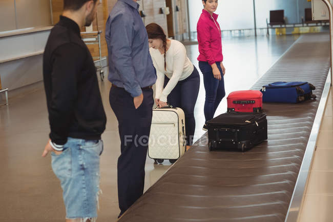 Woman taking her suitcase off the baggage carousel at airport — Stock Photo