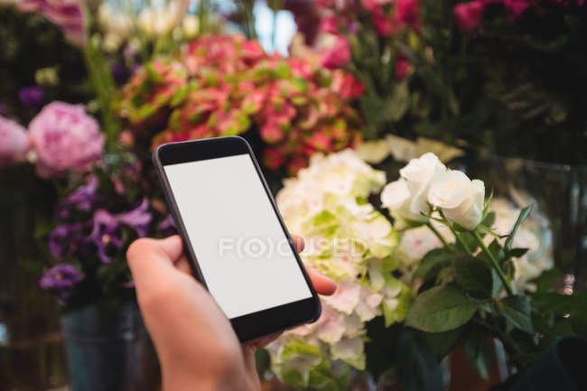 Hand of female florist holding mobile phone in the flower shop — Stock Photo