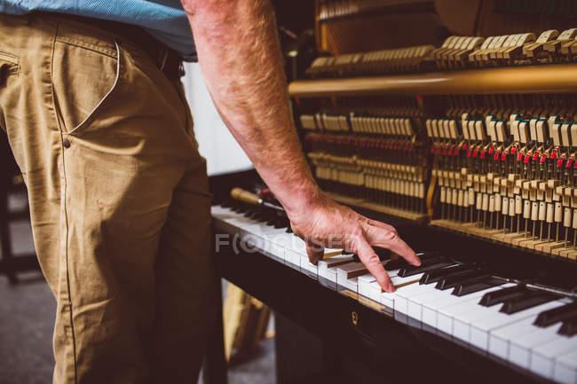 Piano technician repairing retro piano at workshop — Stock Photo