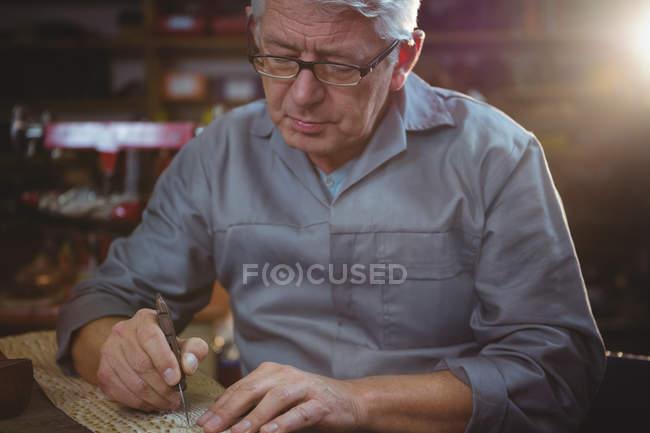 Sapateiro sênior cortando um pedaço de material na oficina — Fotografia de Stock