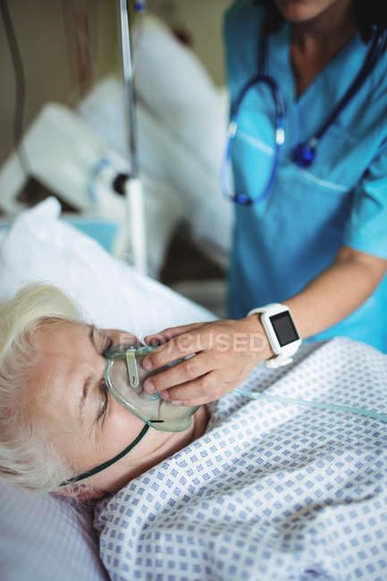 Enfermera poniendo máscara de oxígeno en el paciente en el hospital - foto de stock