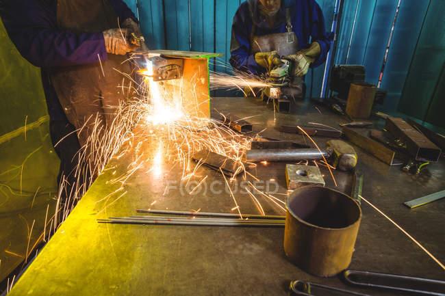 Обрезанный образ мужских и женских сварщиков, работающих вместе в мастерской — стоковое фото