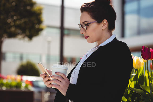 Young businesswoman holding mobile phone and disposable coffee cup — Stock Photo