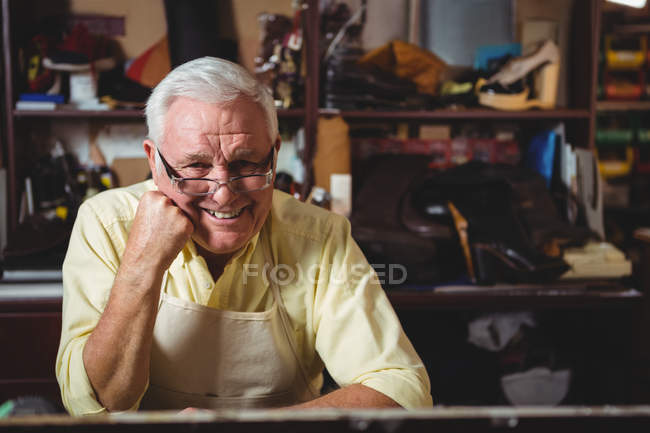 Portrait of shoemaker sitting in workshop with hand on chin — стокове фото