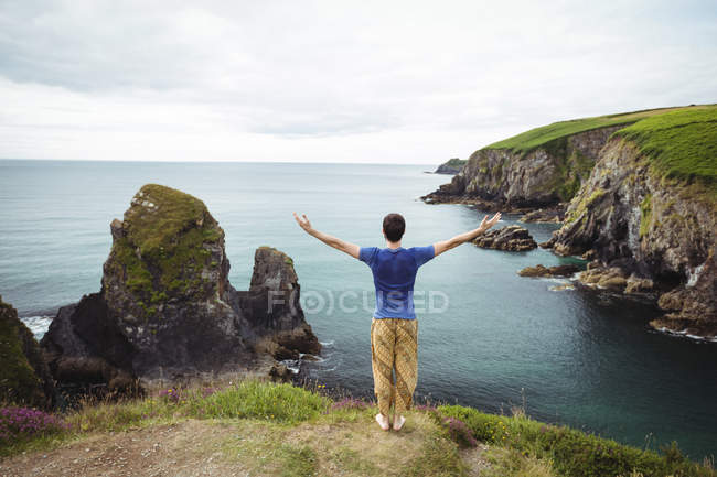 Rear view of man standing with arms outstretched on cliff — Stock Photo