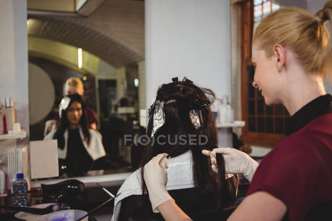 Female hairdresser dyeing hair of her client in salon — Stock Photo