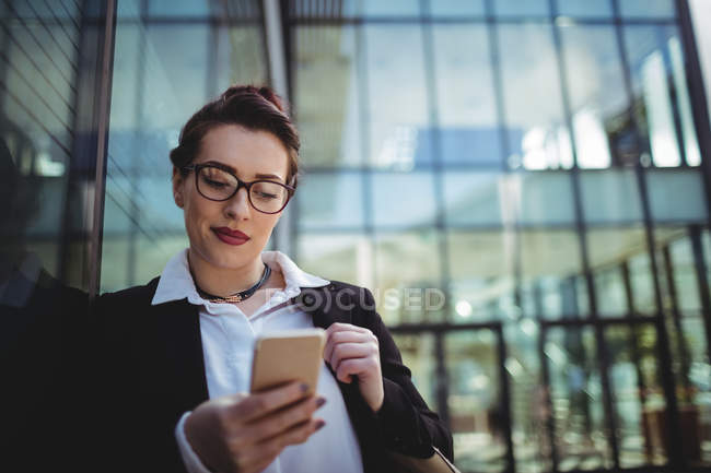 Young businesswoman using mobile phone outside office — Stock Photo