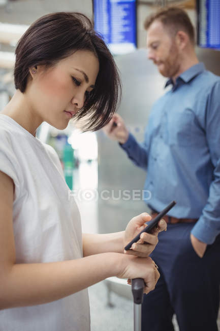 Business people using mobile phones in airport terminal — Stock Photo