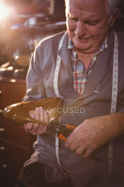 Shoemaker repairing a high heel in workshop — Stock Photo