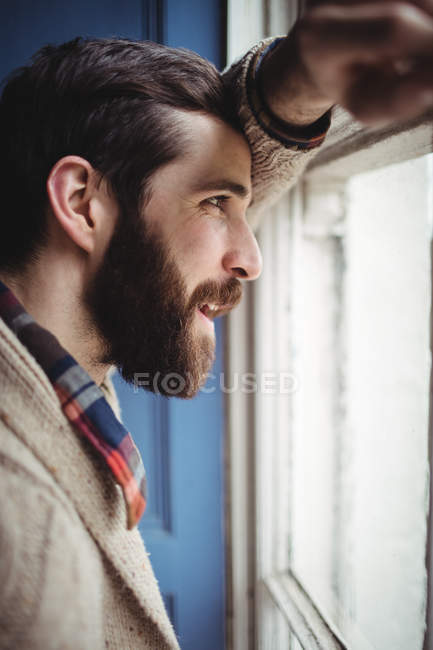 Man looking through window at home — Stock Photo
