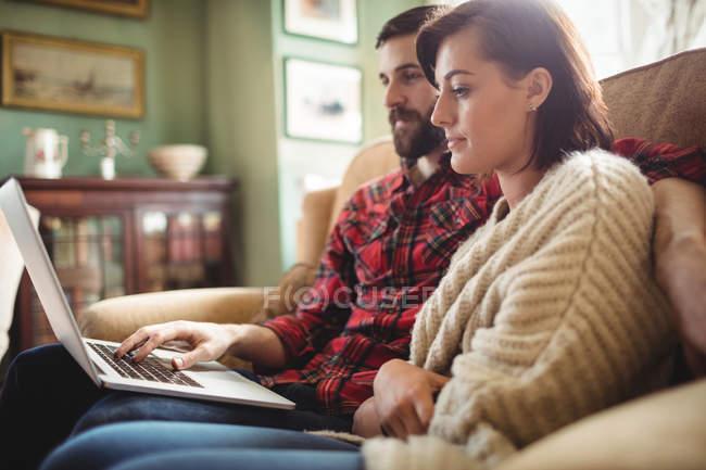 Junges Paar benutzt Laptop im heimischen Wohnzimmer — Stockfoto