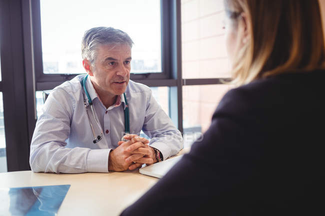 Doctor at desk talking to patient in hospital — Stock Photo