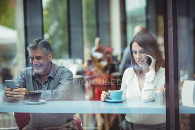 Testo di uomo messaggistica mentre la donna parla al cellulare in caffetteria — Foto stock