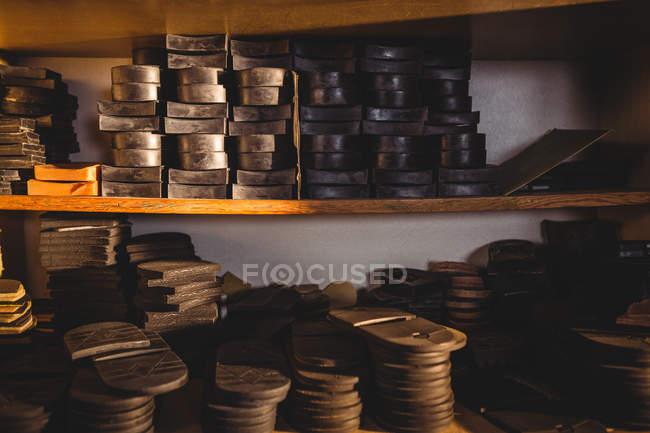 Empilements de semelles intérieures de chaussures en cuir dans les étagères de l'atelier de fabrication de chaussures — Photo de stock