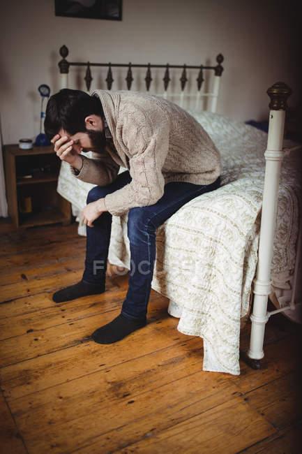 Депрессивный мужчина сидит на кровати в спальне — стоковое фото