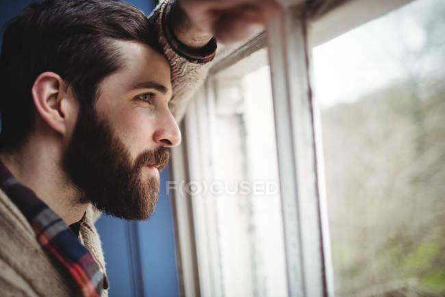 Чоловік дивиться через вікно на дому — стокове фото