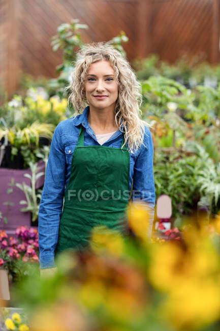 Портрет жіноче флорист, посміхаючись в садовому центрі — стокове фото
