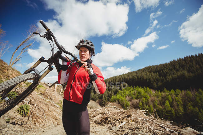Байкер с велосипедом на горе против неба — стоковое фото