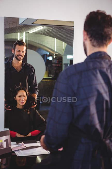 Beau coiffeur avec client au salon de coiffure — Photo de stock
