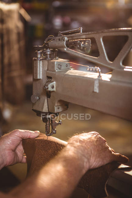 Hands of shoemaker using sewing machine in workshop — Stock Photo