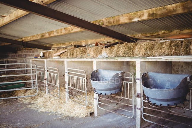 Hay and food containers in old barn building — Stock Photo