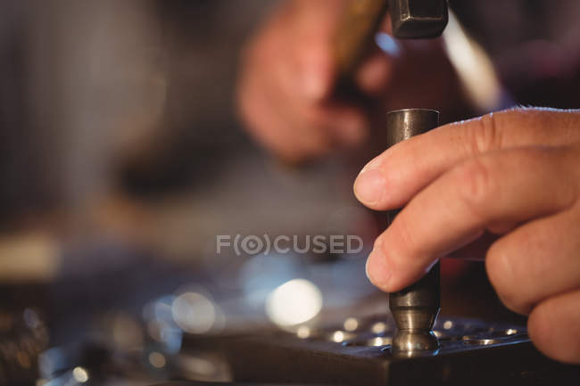 Cropped image of goldsmith making hole in sinking at workshop — Stock Photo