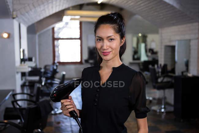 Ritratto di parrucchiera sorridente che tiene l'asciugacapelli nel salone di parrucchiere — Foto stock
