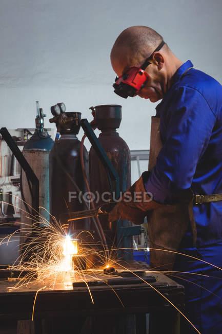 Soldador macho trabajando en pieza de metal en taller - foto de stock