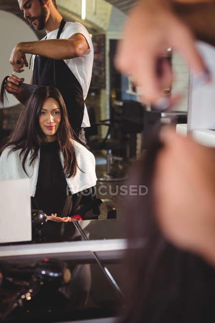 Femme se faire couper les cheveux avec des ciseaux dans le salon — Photo de stock