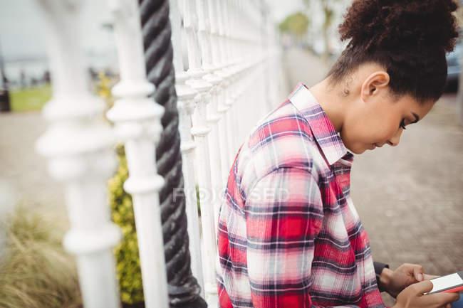 Vista laterale della donna utilizzando smartphone mentre si appoggia sulla ringhiera — Foto stock