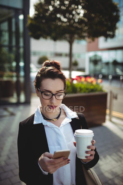 Young businesswoman with disposable coffee cup using mobile phone on street — Stock Photo