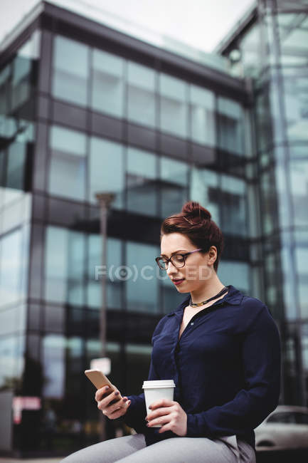 Young woman using mobile phone against office building — Stock Photo