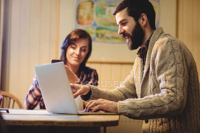 Couple interacting while using laptop and mobile phone at home — Stock Photo