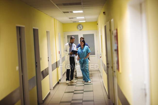 Arzt und Krankenschwester tauschen sich über Bericht im Krankenhausflur aus — Stockfoto