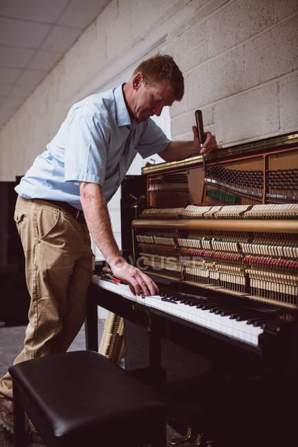 Piano technician repairing vintage piano at workshop — Stock Photo