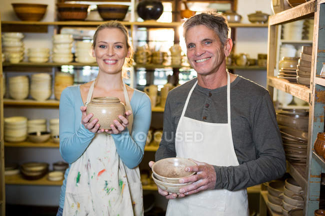 Portrait of happy potters holding pottery in workshop — Stock Photo