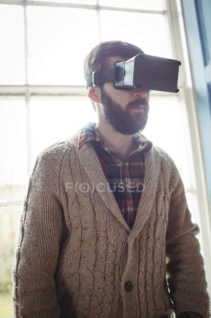 Young man using virtual glasses at home near window — Stock Photo