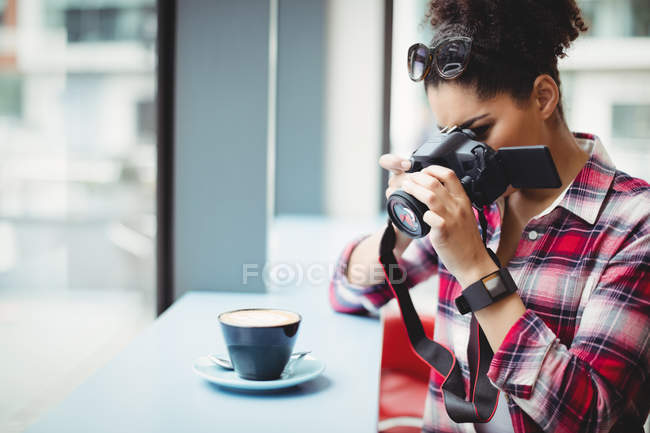 Woman photographing coffee while standing at restaurant — Stock Photo