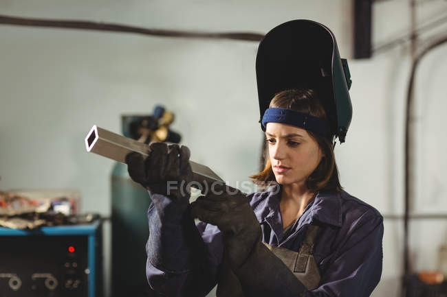 Schweißerin begutachtet Metallstück in Werkstatt — Stockfoto