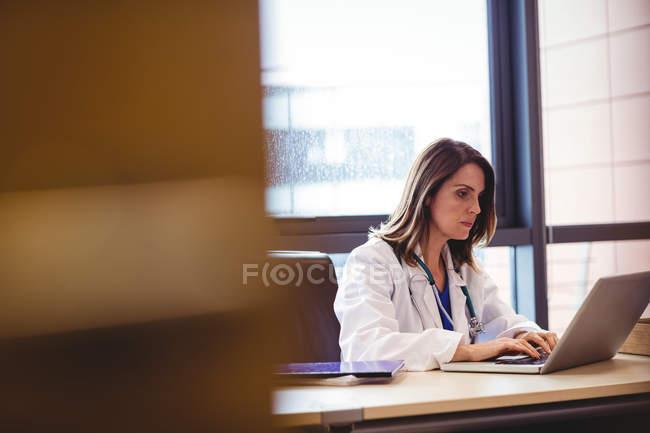 Médica feminina usando laptop na mesa no hospital — Fotografia de Stock