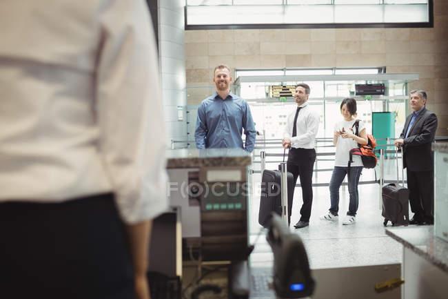 Passagiere stehen am Check-in-Schalter im Flughafenterminal Schlange — Stockfoto