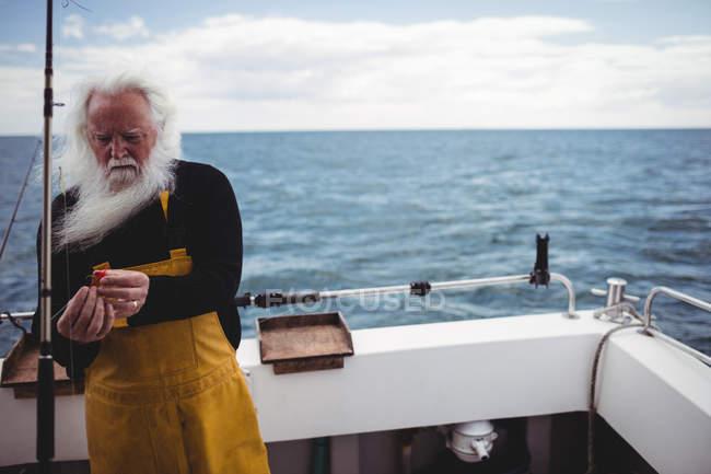 Fischer bereitet Angelrute auf Fischerboot vor — Stockfoto