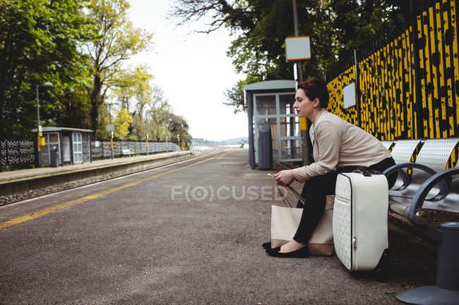 Frau wartet in voller Länge auf Bank am Bahnhof — Stockfoto
