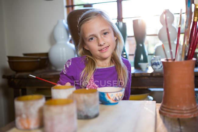Porträt eines lächelnden Mädchens am Tisch in der Töpferei — Stockfoto